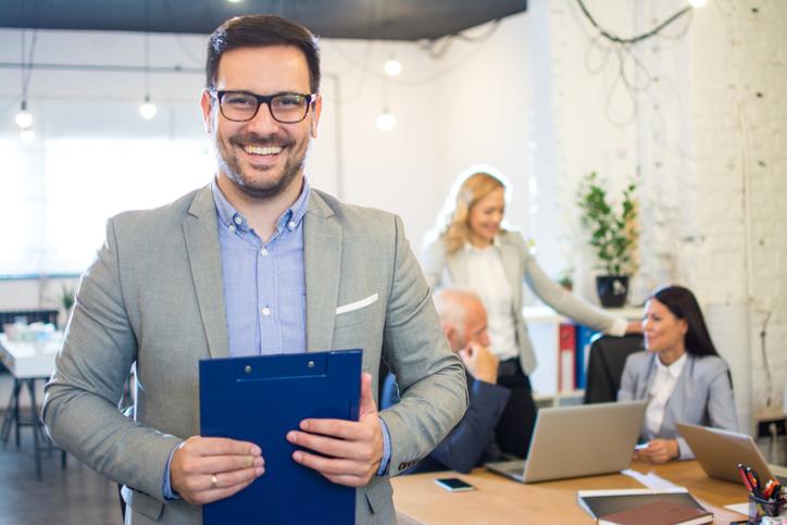 Smiling businessman holding folder in office